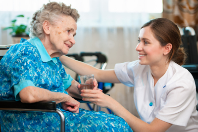 caregiver giving one glass of water to senior woman