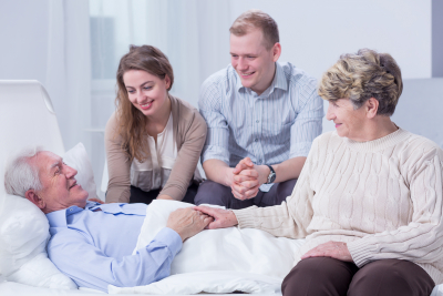 senior man lying on bed with his doctor and relatives